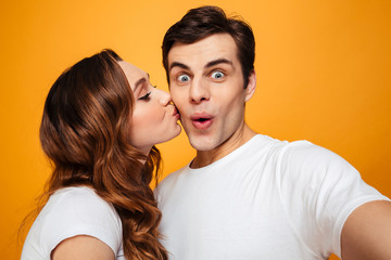 Portrait of two people making selfie while woman kissing her boyfriend in cheek, over yellow background
