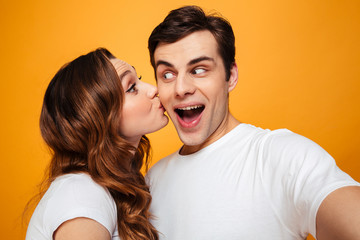 Display of affection of adorable couple, girlfrined kissing her man in cheek over yellow background