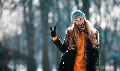 Young woman at sunny winter day outdoor showing V sign