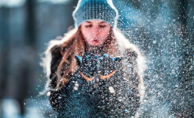 Winter woman blowing snow outdoor, flying snowflakes