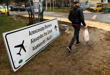A man passes a sign for Alexander the Great Airport which was removed due to road construction in Skopje