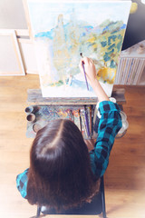 Ispirtional activity. Creative young girl in a casual attire sitting straight while taking part in a painting class and using bright oil paints in an art studio.