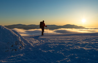 Hiker walking on snowshoes in the snowcovered mountains during a colorful, winter sunset. Vercors, France.