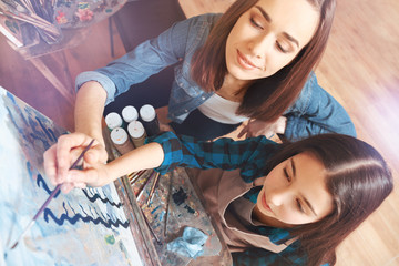 Educative activity. Talented painter and a focused teenage girl working as a team and painting together during a painting session.