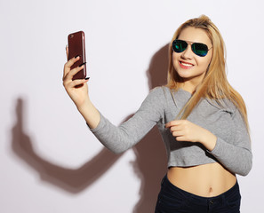 woman making selfie photo on smartphone isolated on a white bac