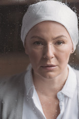 close-up view of sick mature woman in kerchief looking at camera through window with raindrops