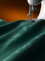 sewing machine needle working on a green damask textile. close-up. detail