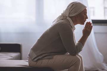 side view of sick mature woman in kerchief praying, cancer concept