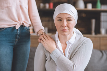 cropped shot of woman supporting sick mature mother in kerchief looking at camera