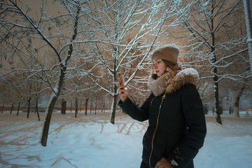 A girl wearing knitted scarf and hat, watching on phone screen in winter park