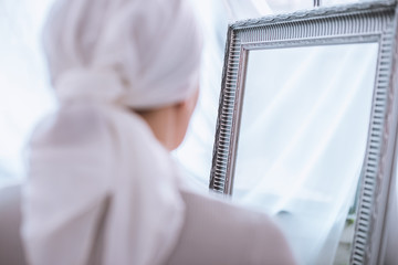 back view of sick woman in kerchief standing near mirror, cancer concept