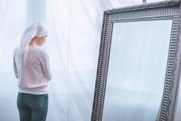 back view of young sick woman in kerchief standing near mirror, cancer concept