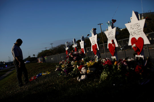 A man mourns next to the crosses and Stars of David placed in front of the fence of the Marjory Stoneman Douglas High School to commemorate the victims of the mass shooting, in Parkland