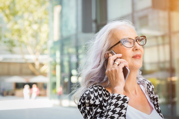 Attractive older woman wearing glasses with long grey hair standing listening to a mobile call in an urban street with a pensive expression