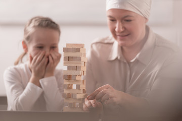 child with sick grandmother in kerchief playing with wooden blocks together