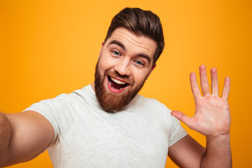 Portrait of a smiling bearded man waving