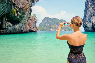 Tourism and vacation in Thailand. Pretty young woman taking picture of beautiful landscape on tropical beach.