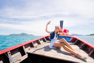 Happy vacation in Thailand. Pretty young woman taking selfie on smartphone sailing the sea on traditional longtail boat.