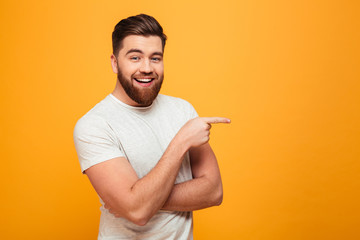 Portrait of a cheerful bearded man pointing finger Wall mural