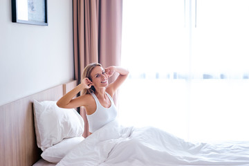 Good morning! Pretty young woman stretching up in bed at home.