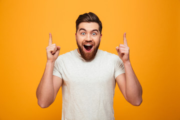 Portrait of a happy bearded man pointing fingers up