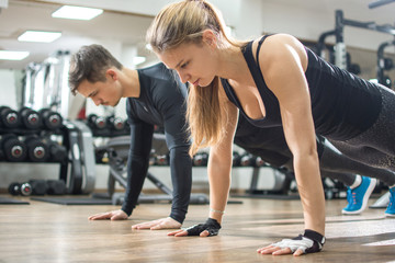 Attractive young woman and man doing push ups in the gym.