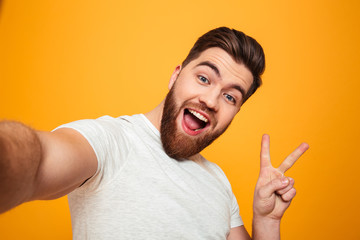 Portrait of a cheerful bearded man showing peace gesture
