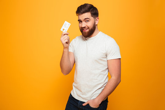 Portrait of a smiling bearded man showing credit card