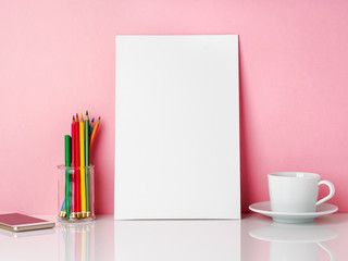 Blank white frame and crayon in jar, cup of coffee r tea on a white table against the pink wall with copy space