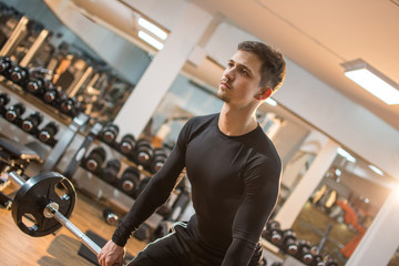 Serious young fitness man lifting barbell in gym