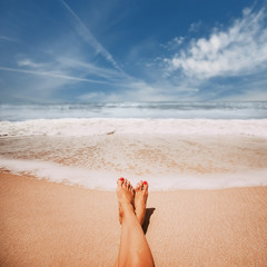 Female feet on sandy ocean  beach. picture with soft focus and place for your text. summer concept