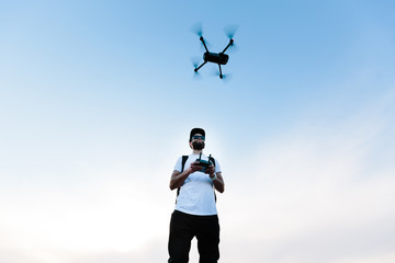 Man flying a drone copter by operating it