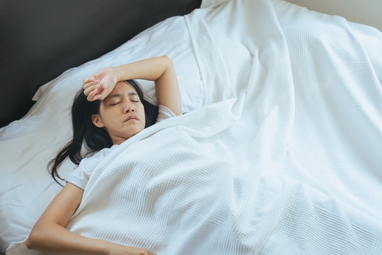 Asian insomnia woman have a headache on bed
