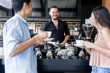 Friendly Asian young bartender cleaning the coffee maker while talking with two young customers over the bar counter of a modern cafeteria