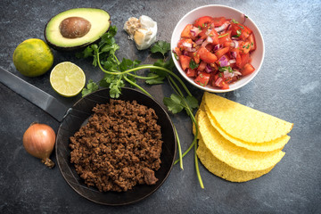 ingredients for mexican tacos with roasted beef tomatoes and avocado on a dark stone background, top view from above
