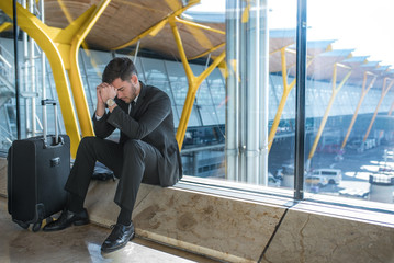 young businessman upset at the airport waiting his delayed flight with luggage