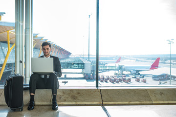 young handsome businessman using his laptop and mobile phone at the airport waiting for his flight and smiling