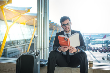 handsome businessman reading a book in the airport sitting close to the window