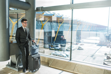 handsome young businessman smiling next to the window with his baggage waiting for his flight