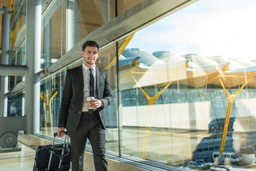 handsome businessman standing waiting for his flight at the airport close to the terminal window