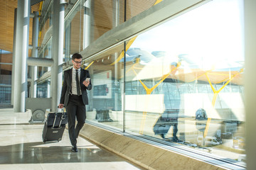 young businessman walking at the airport using his mobile phone