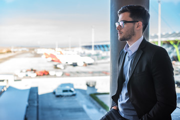 businessman standing at the airport window waiting for his flight with luggage