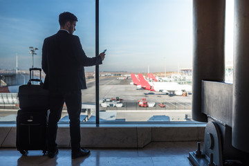 businessman standing at the airport window waiting for his flight with luggage using his mobile phone