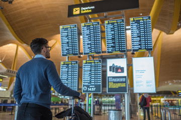 man checking his flight on the timetable display at the airport