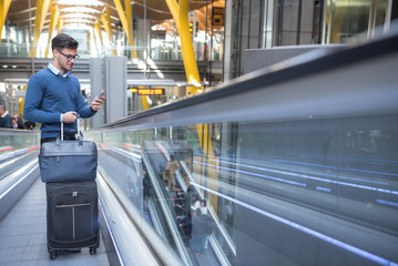young man on the escalator at the airport using his mobile phone with his luggage smiling