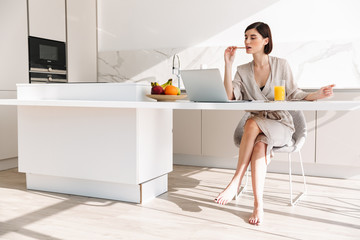 Image of cute brunette woman wearing bathrobe sitting at table in kitchen, and using laptop while having breakfast