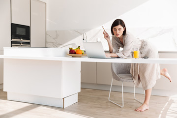Smart concentrated woman in housecoat sitting at table in kitchen, and working on laptop while having breakfast