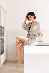 Portrait of sexual elegant woman with short dark hair wearing robe posing in kitchen, sitting on table in sunny morning