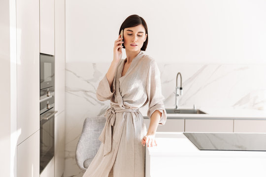 Single woman with short dark hair wearing sexual robe posing in kitchen, and speaking on mobile phone