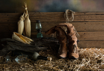 Women's boots on pile straw in the old barn which has dim light / still Life image and selective focus